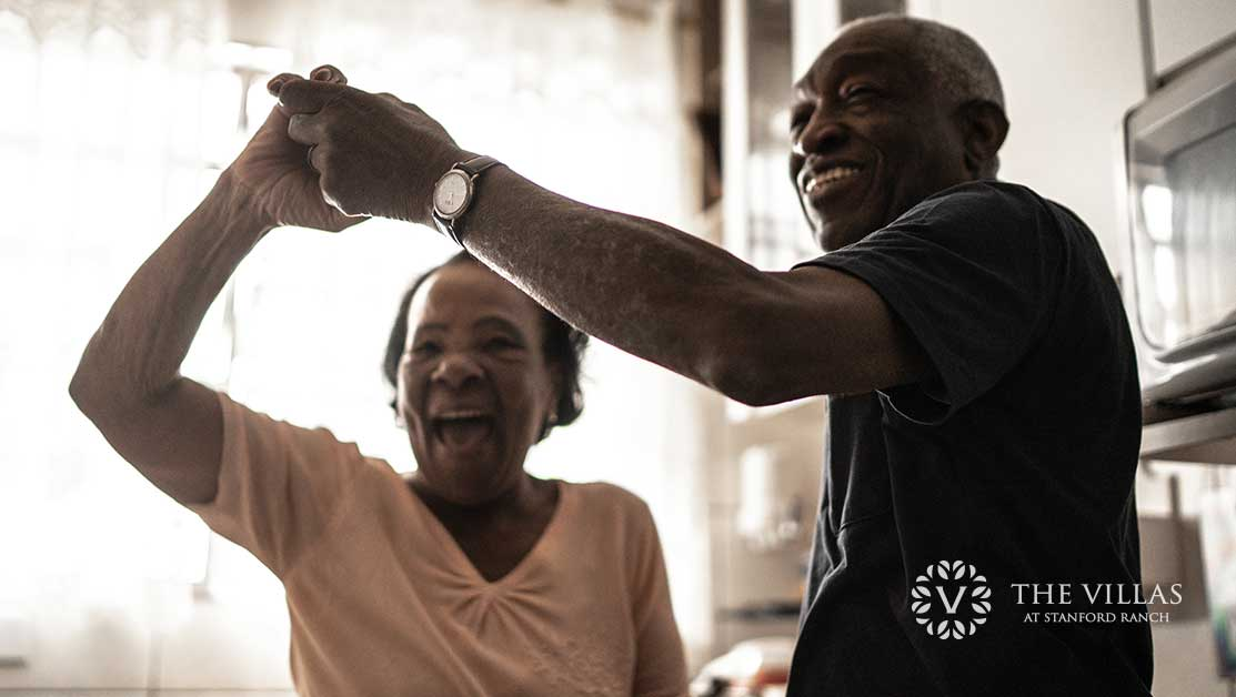 A senior African American couple dancing together. Learn more about enjoying retirement in a senior living facility.